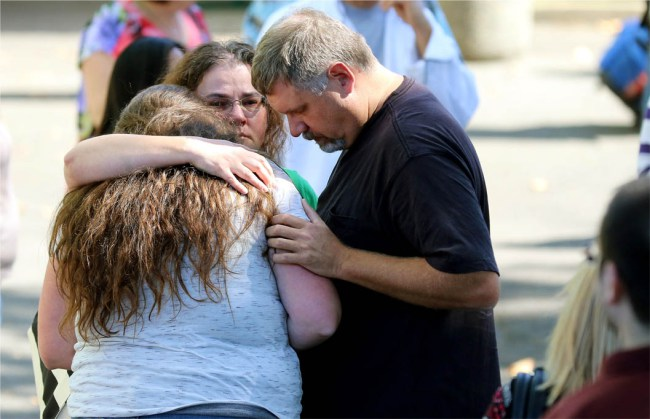 Friends and family are reunited with students at the local fairgrounds after a deadly shooting at Umpqua Community College, in Roseburg, Ore., Thursday, Oct. 1, 2015. (AP Photo/Ryan Kang)