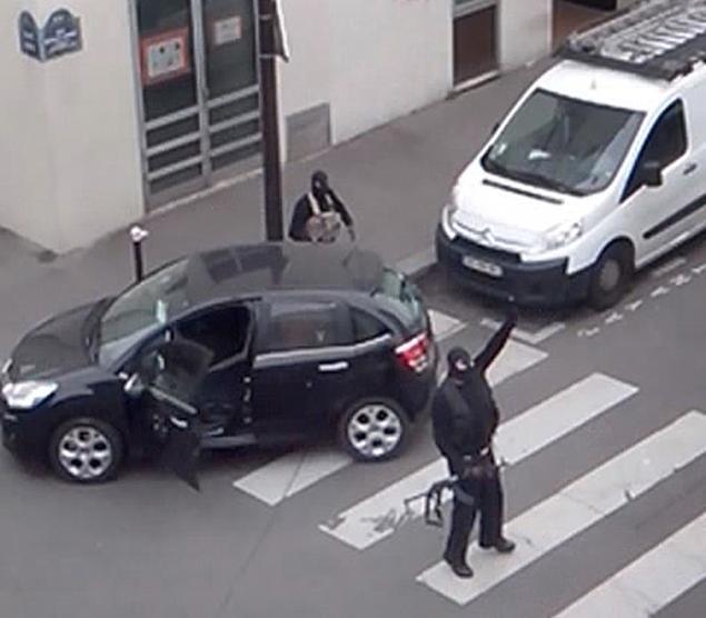 Gunmen standing near car. Photo Courtesy of NY Daily News.