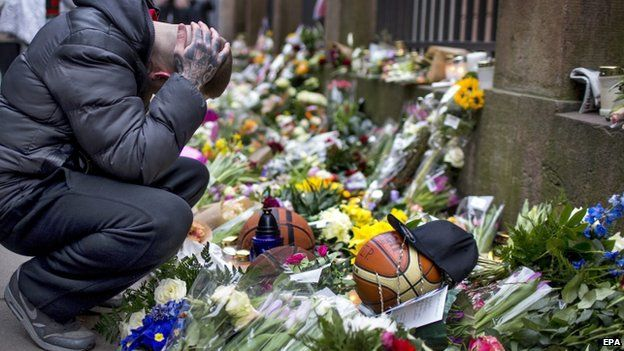 Mourners place flowers outside of synagogue. Photo Courtesy of BBC NEWS.