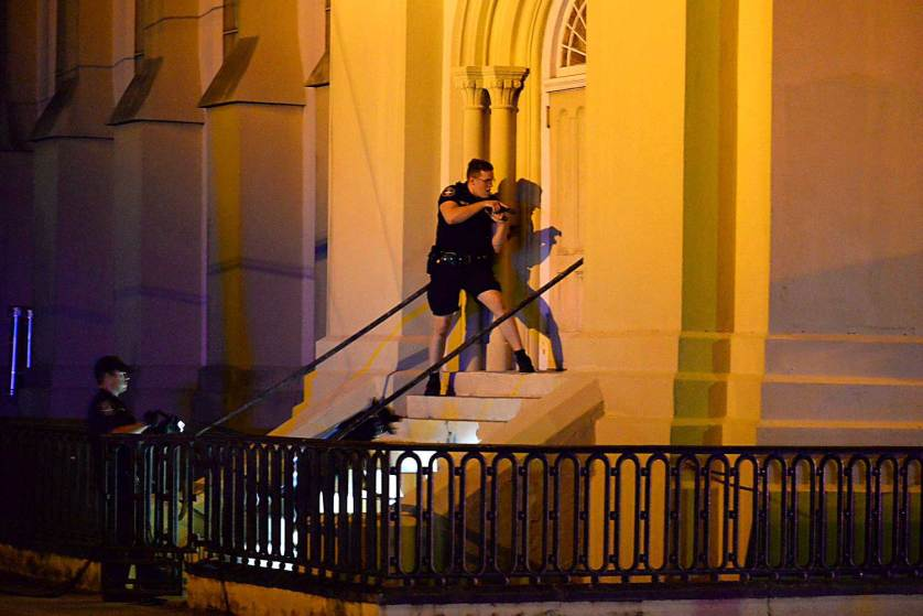 Charleston police officers search for a shooting suspect outside the Emanuel AME Church, in downtown Charleston, S.C. on Wednesday, June 17, 2015. A white man opened fire during a prayer meeting inside the historic black church killing several people. The shooter remained at large Thursday morning. Photo Courtesy of Matthew Fortner/The Post And Courier via AP.