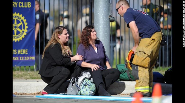 Women speak with firefighter at scene of shooting. Photo Courtesy of CNN.