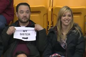 Guy holds up sign during kiss cam at hockey game. Image Courtesy of Youtube.com.