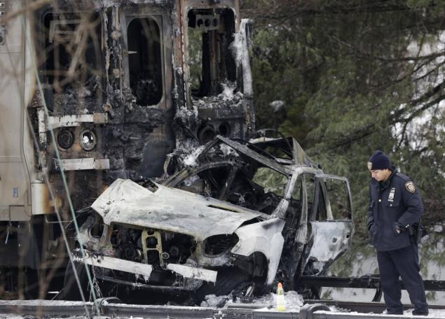 Police officer looks at an SUV that caught fire when struck by a Metro-North train in Westchester County. February 2015. Image Courtesy of nydailynews.com.
